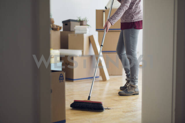 Woman sweeping the floor surrounded by cardboard boxes in an empty room - MAMF00839 - Maria Maar/Westend61