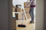 Woman sweeping the floor surrounded by cardboard boxes in an empty room - MAMF00839