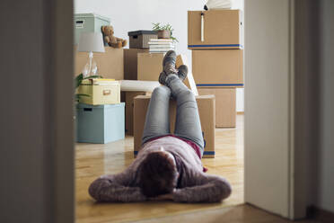 Woman relaxing surrounded by cardboard boxes in a new home - MAMF00842