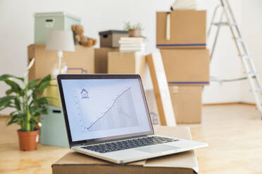 Rising line graph on laptop screen in front of cardboard boxes in an empty room in a new home - MAMF00848