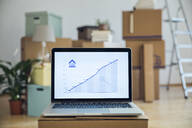 Rising line graph on laptop screen in front of cardboard boxes in an empty room in a new home - MAMF00854
