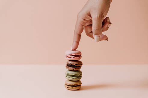 Female hand touching stack of macaroons on pink background - JMHMF00004