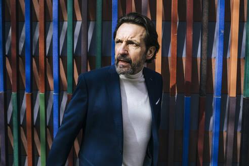 Portrait of mature businessman watching something - JLOF00325