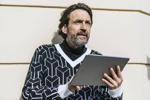 Portrait of fashionable mature man with digital tablet - JLOF00343