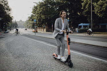 Businessman with e-scooter in the city - JLOF00364