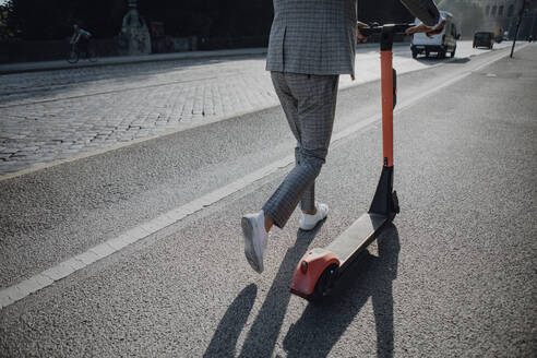 Businessman walking with e-scooter in the city - JLOF00376