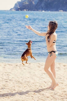 Girl playing with dog on the beach - XCF00283