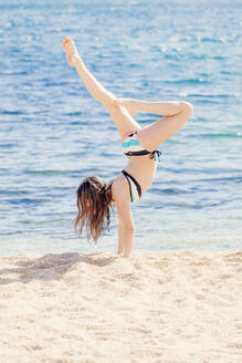 Girl practicing handstand on the beach - XCF00286