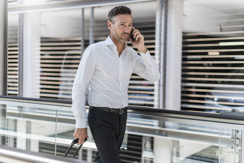 Businessman on escalator talking on the phone - DIGF08460