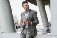 Portrait of businessman with newspaper outdoors - DIGF08496