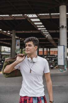 Young man with a bag at train station wearing headphones - JMHMF00014
