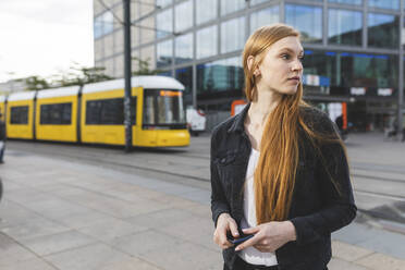 Redheaded young woman waiting at Alexanderplatz, Berlin, Germany - WPEF01999