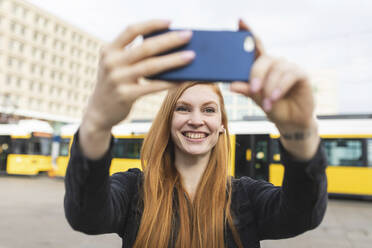 Portrait of redheaded young woman  taking selfie with smartphone, Berlin, Germany - WPEF02005