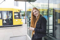 Portrait of redheaded young woman with smartphone in the city, Berlin, Germany - WPEF02008
