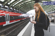 Redheaded young woman with coffee to go waiting at platform using smartphone, Berlin, Germany - WPEF02011