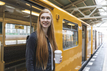 Portrait of redheaded young woman with coffee to go getting out of train, Berlin, Germany - WPEF02014