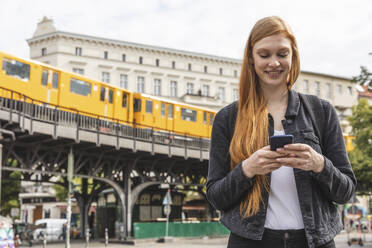 Portrait of redheaded young woman using smartphone, Berlin, Germany - WPEF02017