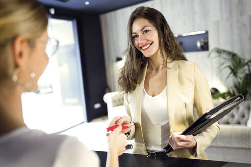 Smiling businesswoman handing over credit card at reception - JSRF00667