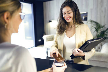 Smiling businesswoman paying contactless with smartphone at reception - JSRF00670