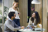 Three happy business people having a meeting in modern office - JSRF00685