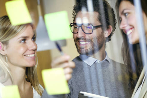 Three smiling business people brainstorming together with sticky notes on a glass wall - JSRF00688