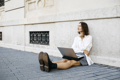 Businesswoman sitting on ground in the city, using laptop - JRFF03766