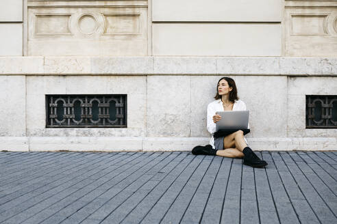 Businesswoman sitting on ground in the city, using laptop - JRFF03769