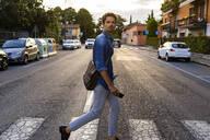 Man crossing street in the city - GIOF07168