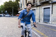 Man riding bicycle in the city - GIOF07174