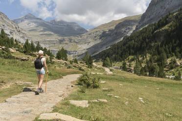 Rear view of woman walking on a trail in mountains, Ordesa national park, Aragon, Spain - AHSF00855