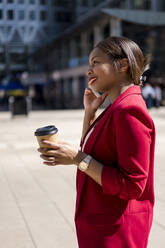 Smiling businesswoman with coffee to go on the phone, London, UK - MAUF02940