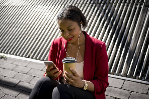Smiling businesswoman with coffee to go using mobile phone and earbuds, London, UK - MAUF02943