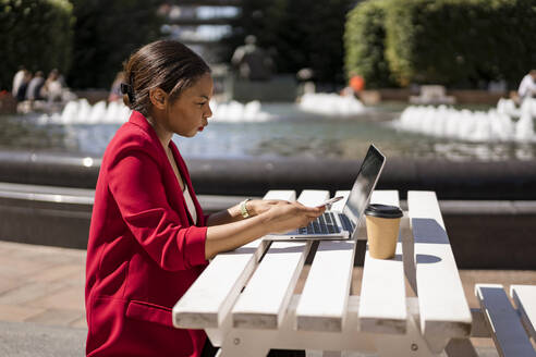 Businesswoman working on laptop outdoors, London, UK - MAUF02949