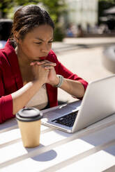 Businesswoman working on laptop outdoors, London, UK - MAUF02952
