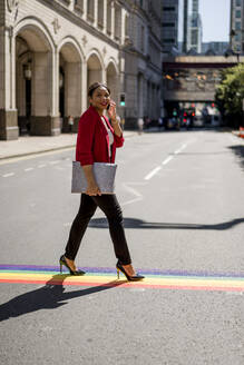 Portrait of businesswoman on the phone crossing the street on LGBT stripes, London, UK - MAUF02958
