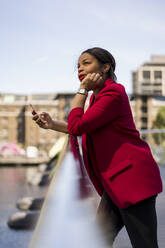 Portrait of pensive businesswoman leaning on bridge railing looking up, London, UK - MAUF02961