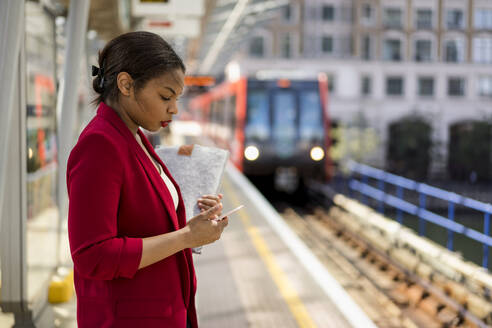 Businesswoman standing on platform looking at mobile phone, London, UK - MAUF02964