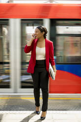 Portrait of laughing businesswoman on the phone standing on platform, London, UK - MAUF02967