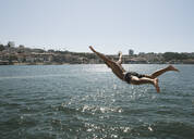 Young man jumping into the water, Porto, Portugal - AHSF00860