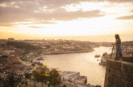 Woman watching panoramic view of Porto at sunset, Portugal - AHSF00863