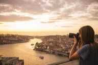 Woman taking a photo of Porto at sunset, Portugal - AHSF00866