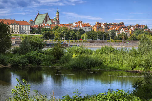 Poland, Masovian Voivodeship, Warsaw, Overgrown riverbank of Vistula river with skyline of Warsaw Old Town in background - ABOF00443