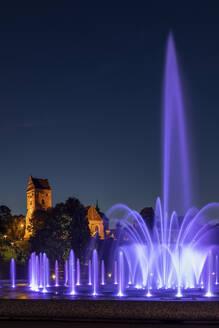 Poland, Masovian Voivodeship, Warsaw, Purple fountain in Multimedia Fountain Park at night with Saint Marys Church in background  - ABOF00449