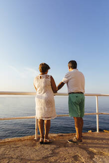 Rear view of senior couple at viewpoint at the coast, El Roc de Sant Gaieta, Spain - MOSF00001
