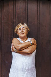 Portrait of a senior woman in front of a wooden door - MOSF00019