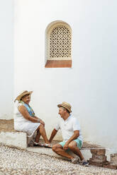 Happy senior tourist couple sitting on steps in a village, El Roc de Sant Gaieta, Spain - MOSF00022