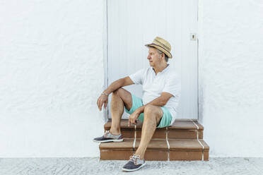 Senior tourist sitting on stoop in a village, El Roc de Sant Gaieta, Spain - MOSF00025