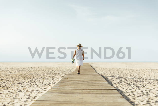Senior woman walking on boardwalk on the beach, El Roc de Sant Gaieta, Spain - MOSF00028 - Marcos Osorio/Westend61