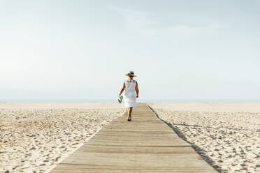 Senior woman walking on boardwalk on the beach, El Roc de Sant Gaieta, Spain - MOSF00028