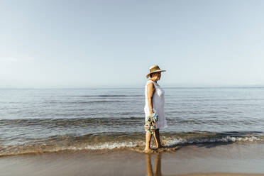 Senior woman wading in the sea, El Roc de Sant Gaieta, Spain - MOSF00031